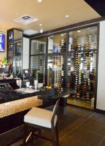 This contemporary commercial custom wine cellar in Las Vegas, Nevada displays the wines in metal wine racks.